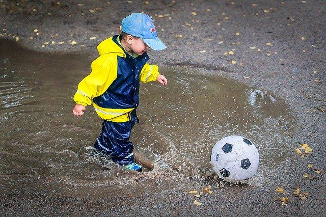 雨の中サッカーする子供